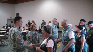 Iowa National Guardsmen and women greet the riders for lunch at Camp Dodge